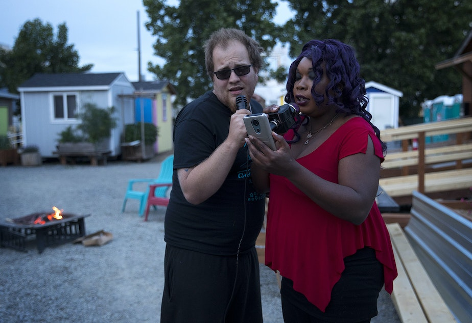 caption: Travis, left, and Ciara, right, sing Summer Lovin' during karaoke on Sunday, June 9, 2019, at the Georgetown Tiny House Village in Seattle.