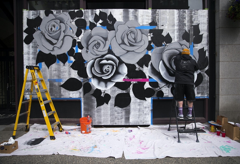 "caption: Artist B Line Dot works on a mural on Tuesday, April 28, 2020, along First Avenue South in Seattle. The completed mural reads, ""Keep Dreaming."""