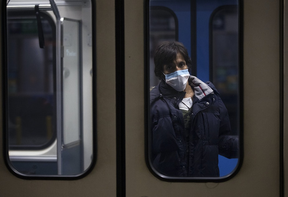 caption: A light rail passenger looks out of the window as it passes through Westlake Station on Thursday, March 26, 2020, in Seattle.