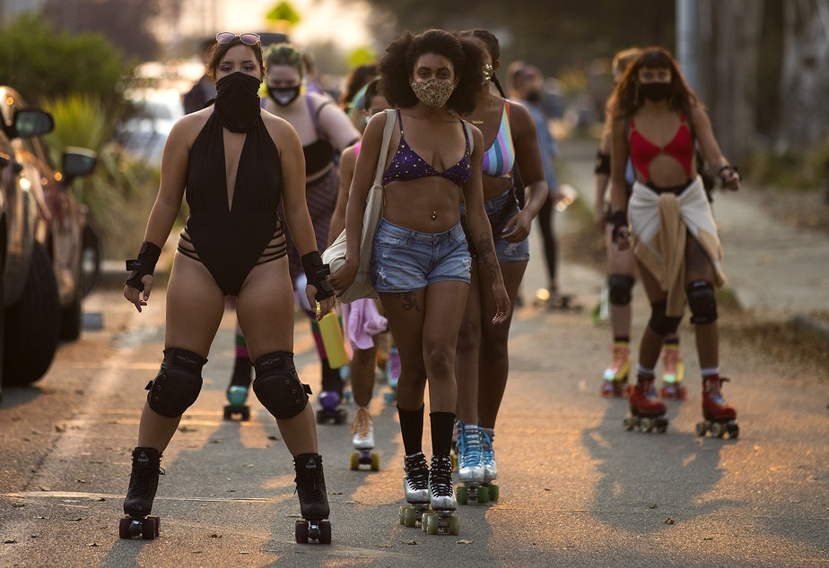 caption: Artemis Peacocke, center, co-founder of Seattle Skates leads a group of roller skaters along Alki Avenue Southwest during a meet up on Wednesday, September 30, 2020, in Seattle.