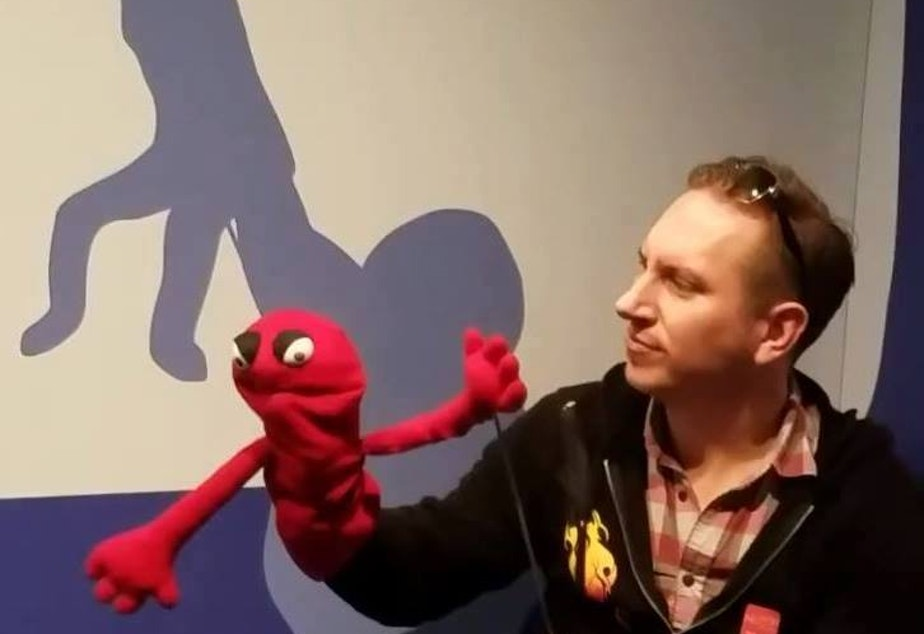 caption: Anthonio Pettit at a Muppet exhibit at MOPOP. As a writer for AIs, Pettit is also a sort of smart speaker puppetmaster.