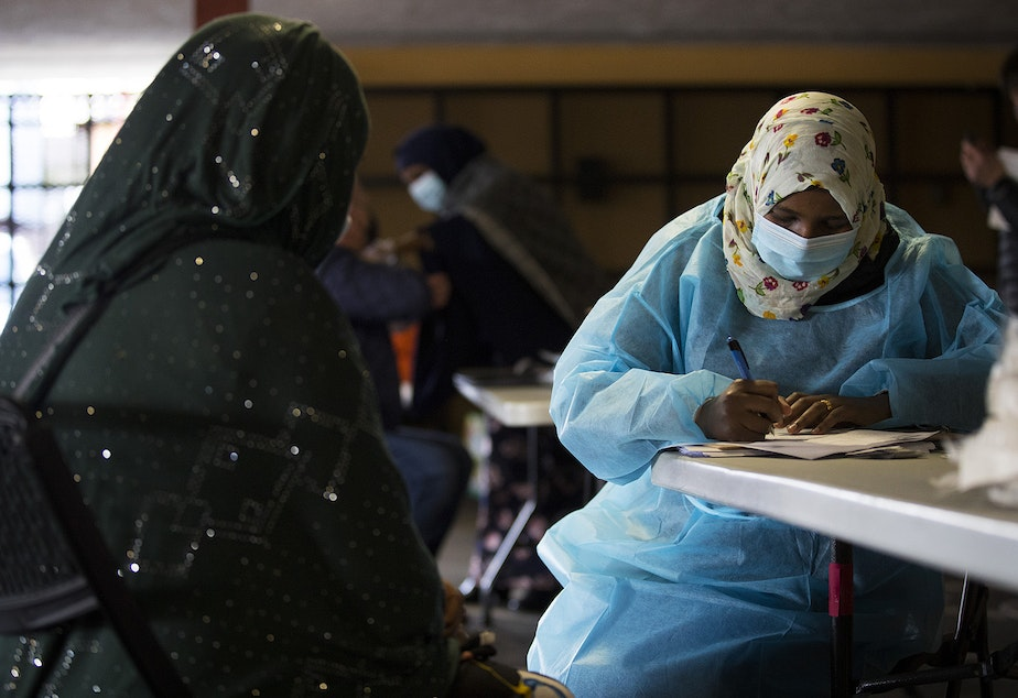 caption: Registered nurse Fartun Mohamed, right, speaks with a community member before administering their first dose of the Moderna Covid-19 vaccine on Wednesday, February 3, 2021, at a vaccine clinic set up by the Somali Health Board to vaccinate 100 seniors at the Brighton Apartments complex on Rainier Avenue South in Seattle.