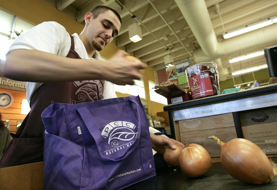Isaiah McDaniel bags groceries into a customer's cloth bags at PCC Natural Market Tuesday, Jan. 15, 2008, in Seattle.