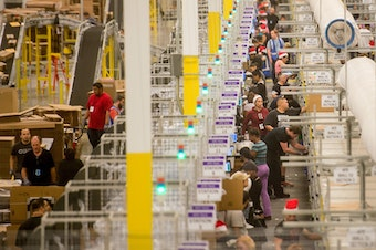 Amazon says it will pay all its U.S. workers at least $15. Here, workers prepare shipments at an Amazon Fulfillment Center in California during the early Christmas rush in 2014.