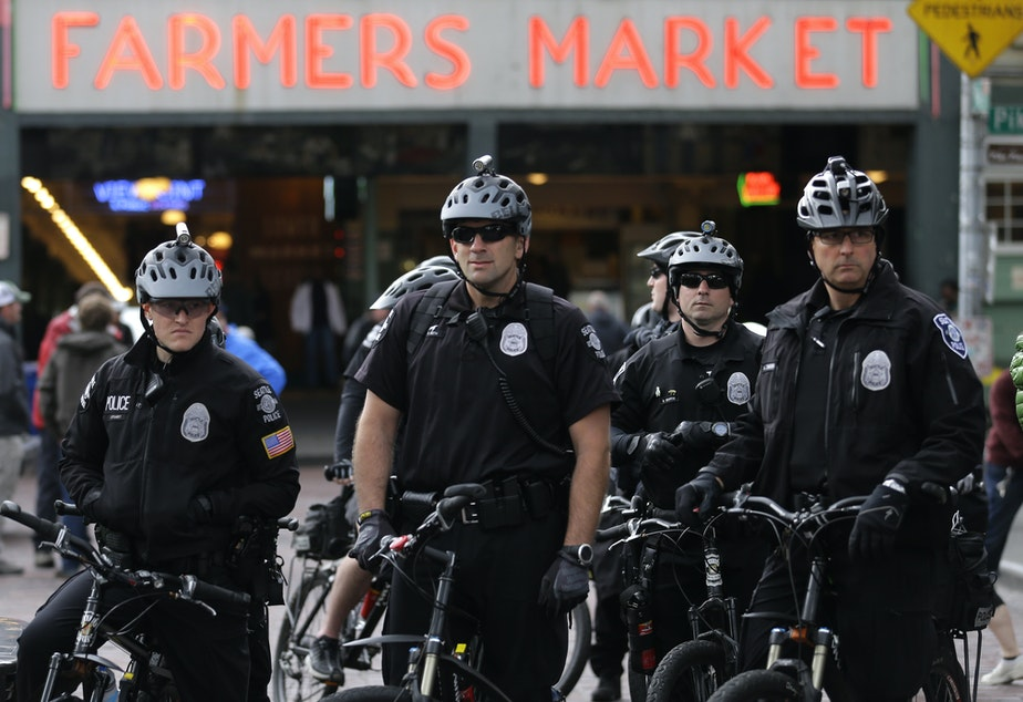 FILE: Seattle Police officers on bicycles wait in a group while monitoring a protest against shootings of unarmed civilians by police, Tuesday, April 14, 2015, in Seattle.