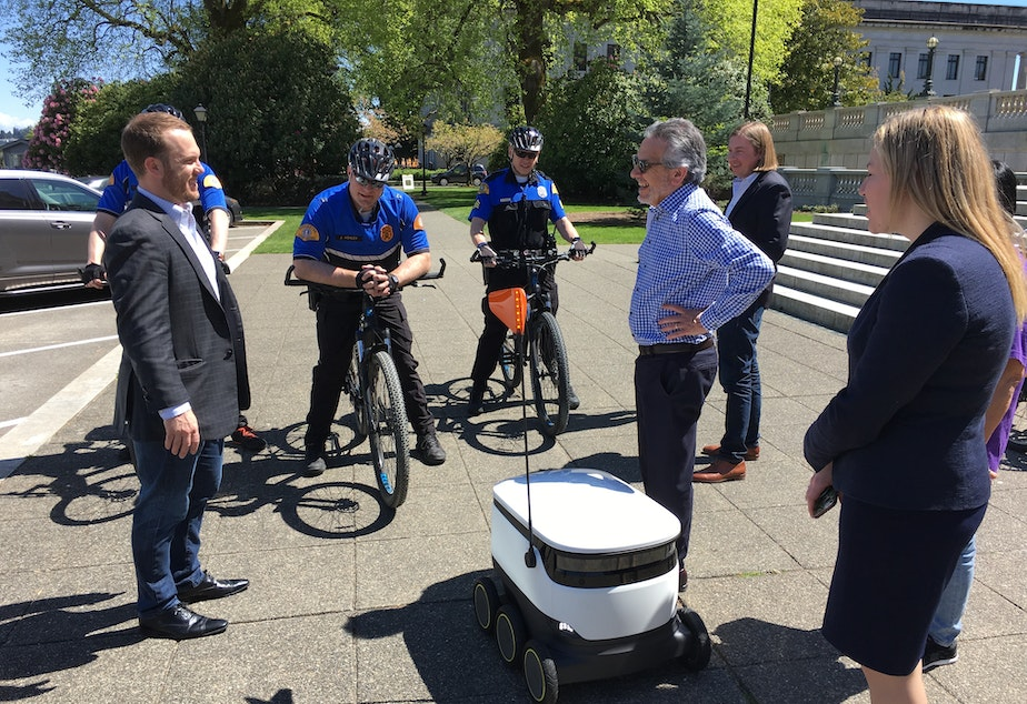 caption: A company rep (left) explains the Starship Technologies sidewalk delivery robot to Gov. Jay Inslee's chief of staff David Postman (center) and curious state troopers in Olympia Tuesday.