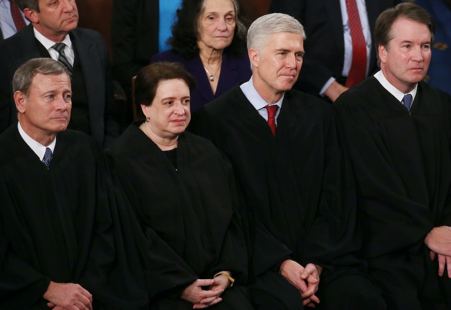 caption: Supreme Court Justices (from left) John Roberts, Elena Kagan, Neil Gorsuch and Brett Kavanaugh attend the State of the Union address on Feb. 4, 2020. In her confirmation hearing, Judge Amy Coney Barrett explained the tradition of judges wearing black robes.