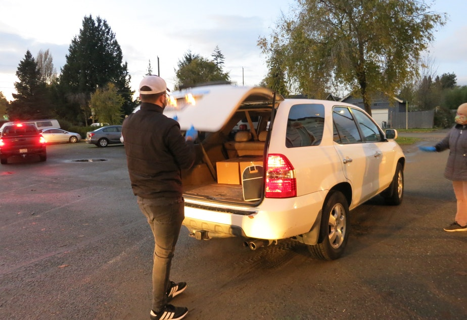 caption: A volunteer at El Dios Viviente church in White Center loads a car with donated food at the church's biweekly distribution event.