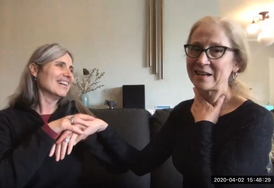 caption: Angela Theriault (at left), director of Seattle Deaf Blind Services, is deaf and almost completely blind. She communicates by touch with her interpreter (at right), Carolyn Traub.