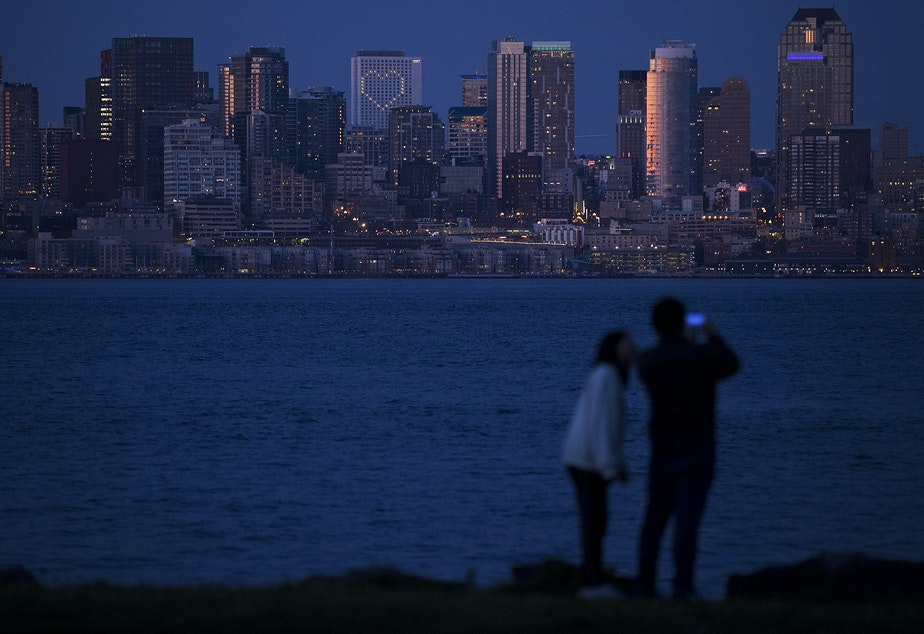 caption: Lit up windows making the shape of a heart at the Hyatt Regency are visible from Sea Crest Park along Harbor Avenue Southwest on Wednesday, April 8, 2020, in Seattle. As of Friday, April 10, the Washington State Department of Health had reported 491 Covid-19 related deaths.