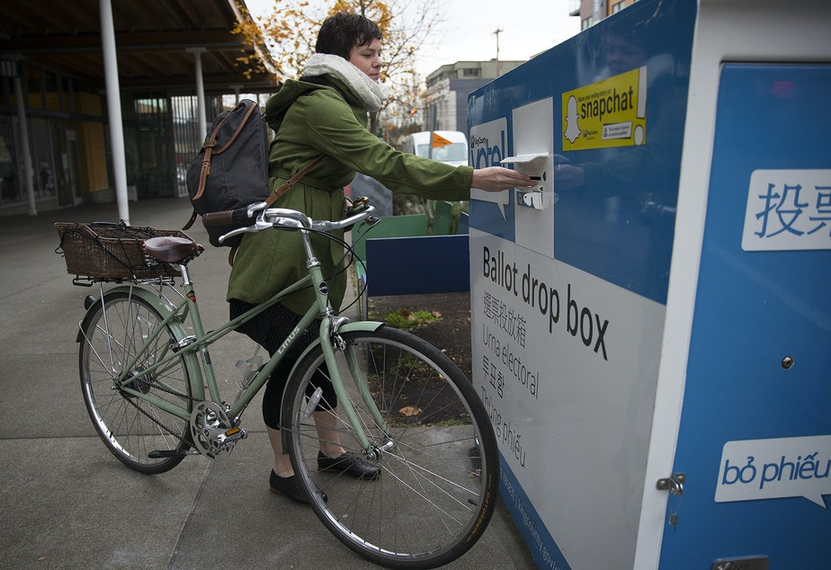 FILE: Siri Anderson drops her ballot into the ballot drop box outside of the Seattle Public Library on Tuesday, November 7, 2017, in Ballard.