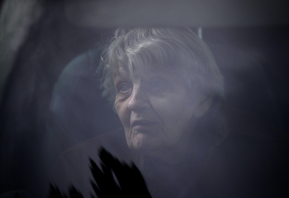 caption: Dorothy Campbell sits in her son's vehicle after knocking on her husband, Gene Campbell's window and speaking to him on the phone at the Life Care Center of Kirkland, the long-term care facility at the epicenter of the first coronavirus outbreak in the U.S., on Thursday, March 5, 2020, in Kirkland. There have been 46 deaths from Covid-19 associated with the facility.