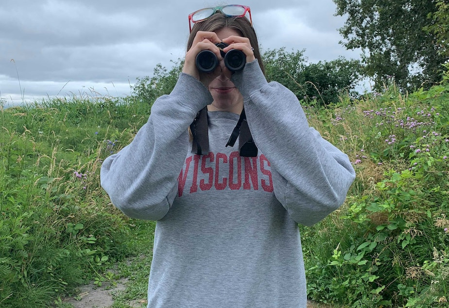 caption: Birder and PhD candidate Olivia Sanderfoot looks through binoculars near the Center for Urban Horticulture in Seattle.