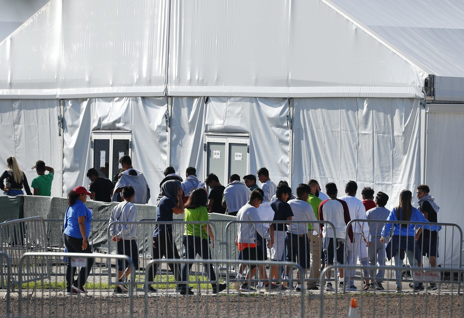 Migrant children line up to enter a tent at the Homestead Temporary Shelter for Unaccompanied Children in Homestead, Fla. in February 2019.