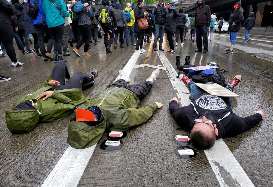 """caption: Activists laid down on I-5 and chanted, """"I can't breathe"""" in honor of George Floyd on Saturday, May 30th, 2020."""