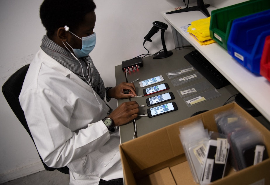 caption: An employee works on smartphones reconditioning in France in January.