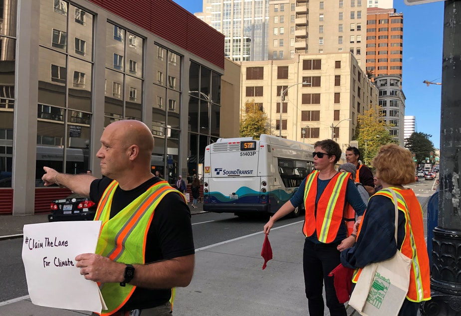 caption: Glen Buhlmann, Meg Wade, and Brie Gyncild of the group 350 Seattle take to the streets on September 26, 2019 to remind car drivers to stay out of the bus lane nearFifth Avenue and Olive Way.