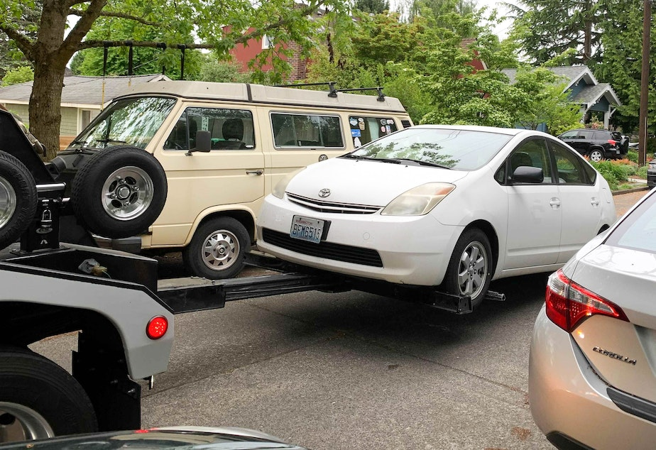 caption: A Prius gets towed in Greenwood on May 17, 2021, after its catalytic converter was stolen from under it the week before. The tow truck driver said he tows three or four cars a day that have had their catalytic converters stolen.