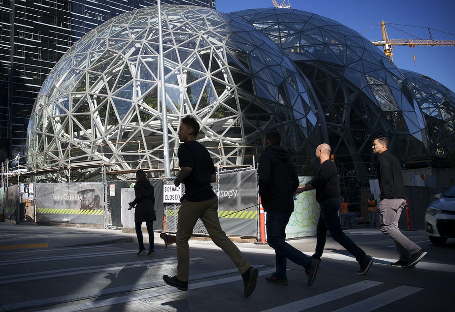 A group of people jog across Lenora Street, on Thursday, October 5, 2017, in front of Amazon's biodomes, in Seattle.