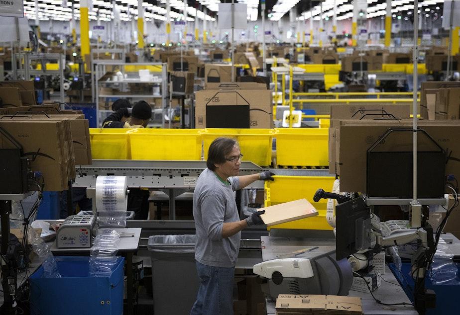 caption: Amazon employee Filomeno Saya packages items at an Amazon fulfillment center on Friday, November 3, 2017, in Kent.