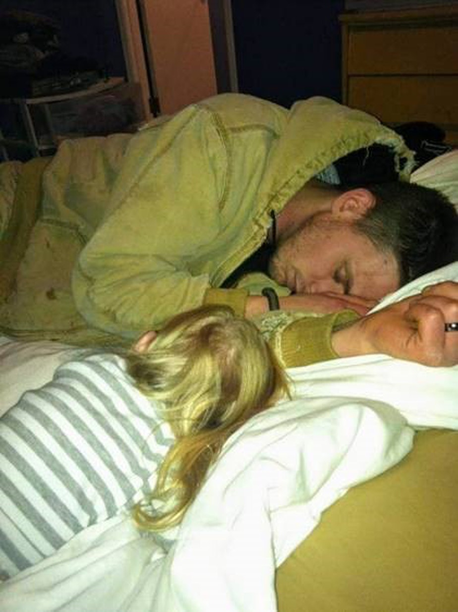caption: Jeremy Lavender asleep with his daughter in 2011.