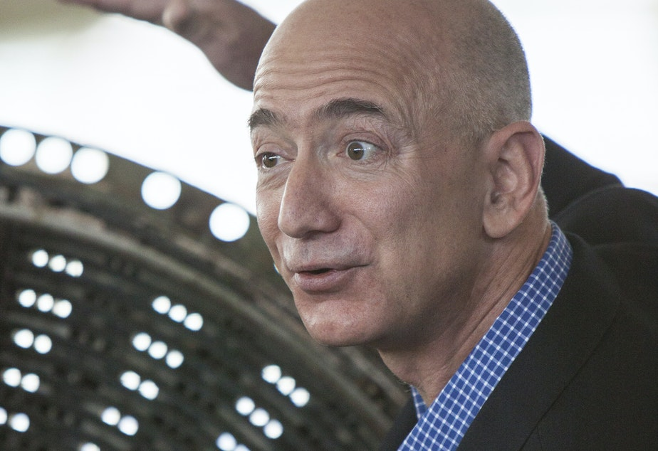 caption: Jeff Bezos speaks at the Apollo rocket engine unveiling at The Museum of Flight, showing the injector plate from an F-1 rocket used on Apollo 12.