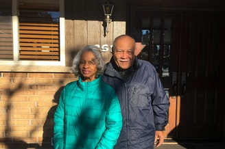 Violet and Norward Brooks in front of a house they struggled to buy due to discrimination.