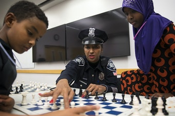 """From left, Kirubel Daniel, 8, Detective Denise """"Cookie"""" Bouldin and Deeqo Abdullahi, 11, play a game of chess on Tuesday, November 28, 2017, at the Rainier Beach Library in Seattle."""
