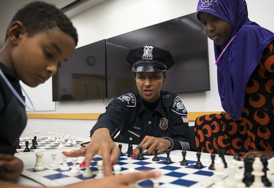 """caption: From left, Kirubel Daniel, 8, Detective Denise """"Cookie"""" Bouldin and Deeqo Abdullahi, 11, play a game of chess on Tuesday, November 28, 2017, at the Rainier Beach Library in Seattle."""