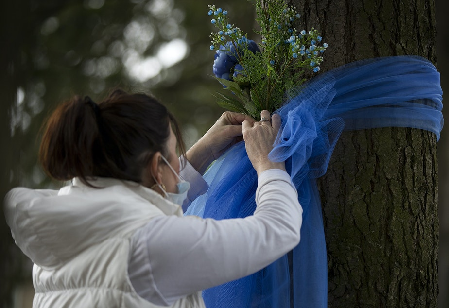 """caption: Tricia LaVoice, of Kirkland, ties blue ribbons and flowers to trees outside of the Life Care Center of Kirkland, the long-term care facility at the epicenter of the coronavirus outbreak in Washington state, on Wednesday, March 11, 2020, in Kirkland. """"Just trying to show them that the community cares,"""" LaVoice said. """"Love really is a big part of healing."""""""