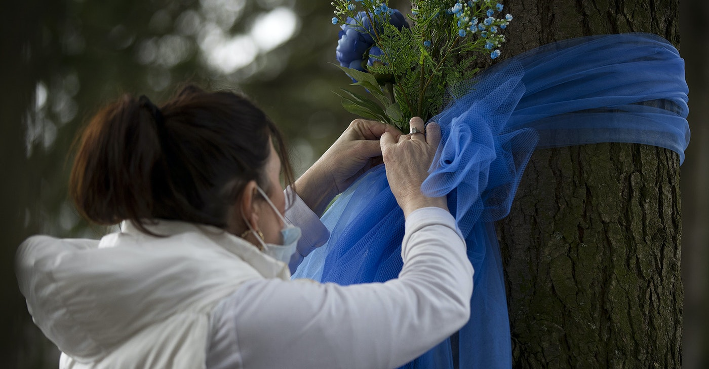 "caption: Tricia LaVoice, of Kirkland, ties blue ribbons and flowers to trees outside of the Life Care Center of Kirkland, the long-term care facility at the epicenter of the coronavirus outbreak in Washington state, on Wednesday, March 11, 2020, in Kirkland. ""Just trying to show them that the community cares,"" LaVoice said. ""Love really is a big part of healing."""