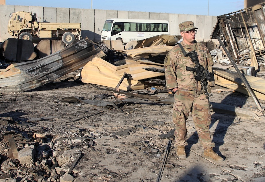 caption: A U.S. soldier stands at a spot struck by a barrage of Iranian missiles at Ain al-Asad air base, in Anbar, Iraq, in January. The attack was in retaliation for the U.S. drone strike that killed Iranian Gen. Qassem Soleimani. The U.S. is drawing down 3,000 troops in Iraq and Afghanistan.