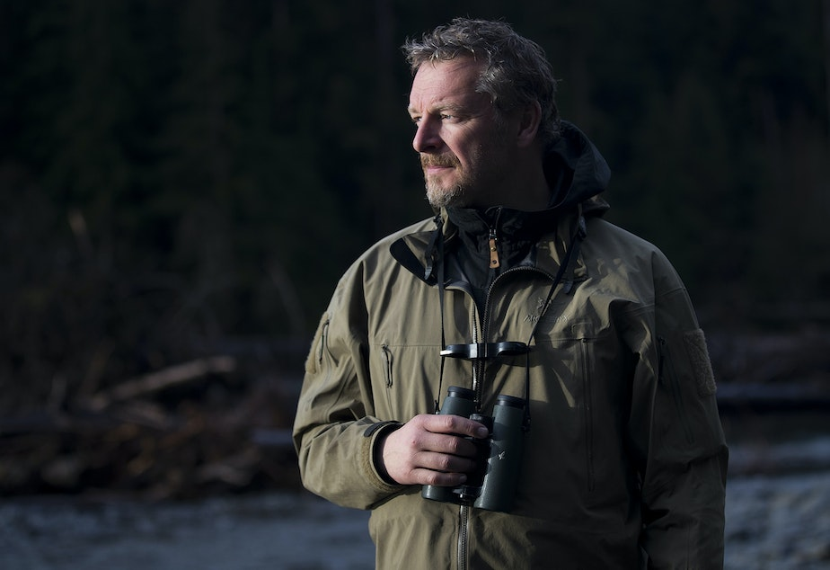 caption: Host of The Wild, Chris Morgan, stands near the Hoh River while hiking to One Square Inch of Silence on Friday, April 5, 2019, in the Hoh Rainforest on the Olympic Peninsula.