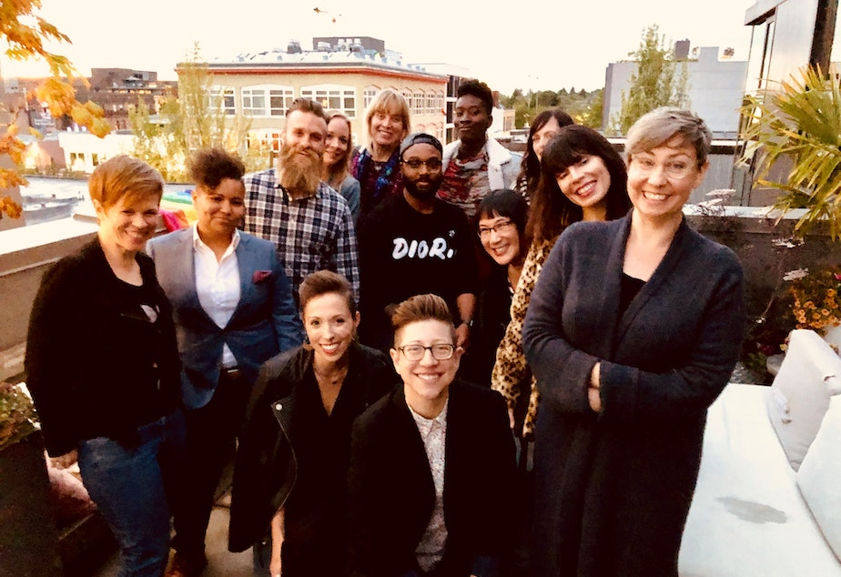 caption: Queeriosity Club 2019. From left to right, standing: Dacia Clay, Mellina White Cusack, Jeffrey Howard, KUOW reporter Ann Dornfeld, Jennifer Hegeman, Timothy Bardlavens, KUOW producer Adwoa Gyimah-Brempong, Christine Cox, Ginger Chien, Amanda Carter Gomes, KUOW producer Jeannie Yandel. Seated: KUOW producer Kristin Leong, Keri Zierler. The Cloud Room in Seattle. June 7, 2019.