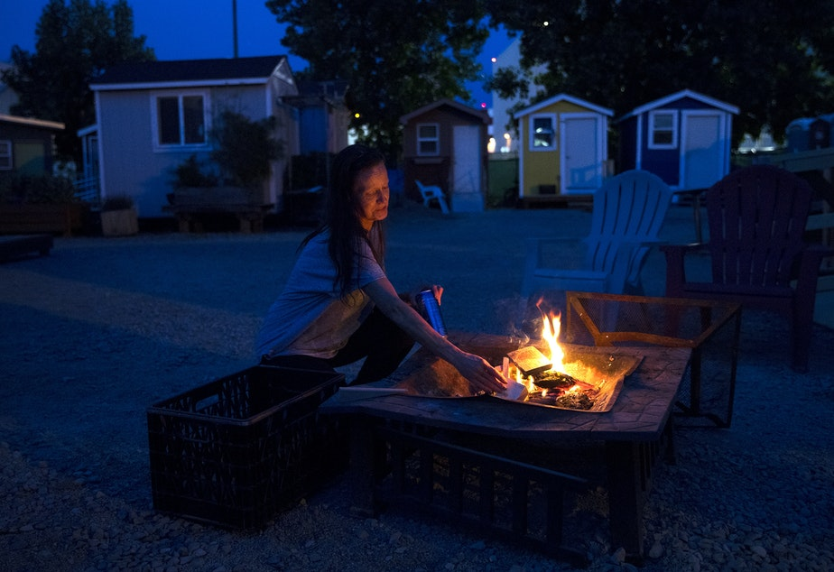 caption: Rebecca adds wood to a fire on Sunday, June 9, 2019, at the Georgetown tiny house village in Seattle.