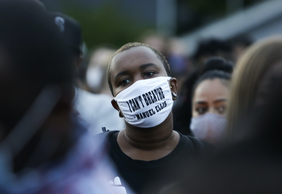 """caption: A man at a vigil this week wears a mask with the words """"I can't breathe"""" above the name of Manuel Ellis, a 33-year-old black man whose death in Tacoma, Wash., police custody was recently ruled a homicide."""