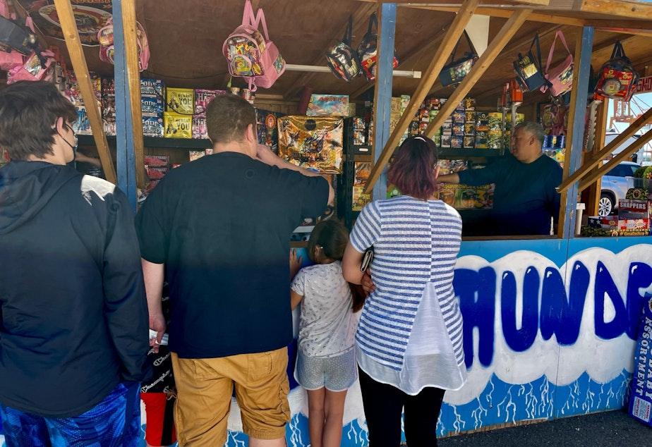 caption: Mark Villegas sells fireworks at the Sons of Thunder stall in Firecracker Alley.