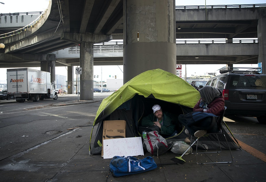 caption: Alex Shpungin talks with a friend, Dorea, right, while sitting in his tent on Tuesday, January 15, 2019, near the intersection of Columbia Street and Alaskan Way South in Seattle. Shpungin has lived at this location for 3 months and hopes to stay there as long as possible.