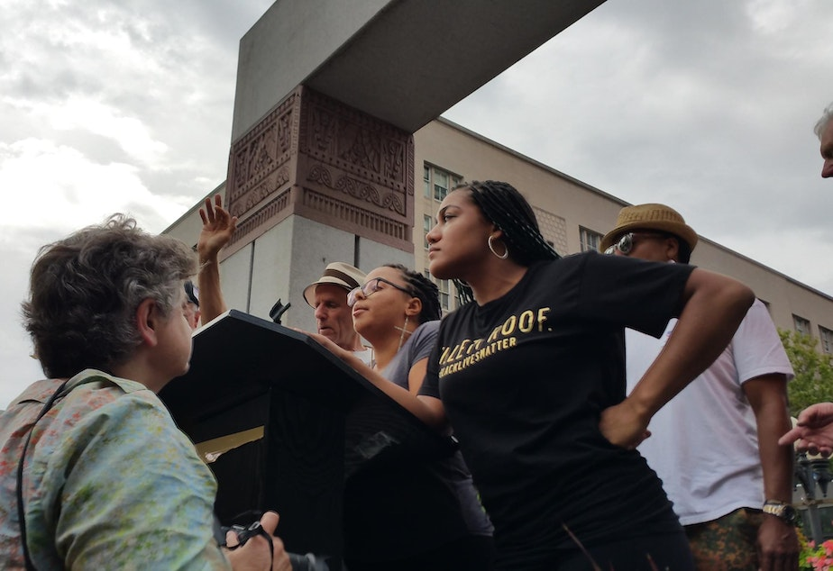 caption: Mara Willaford on the podium at a rally for presidential candidate Bernie Sanders in August. Willaford interrupted the event to call attention to the Black Lives Matter movement.