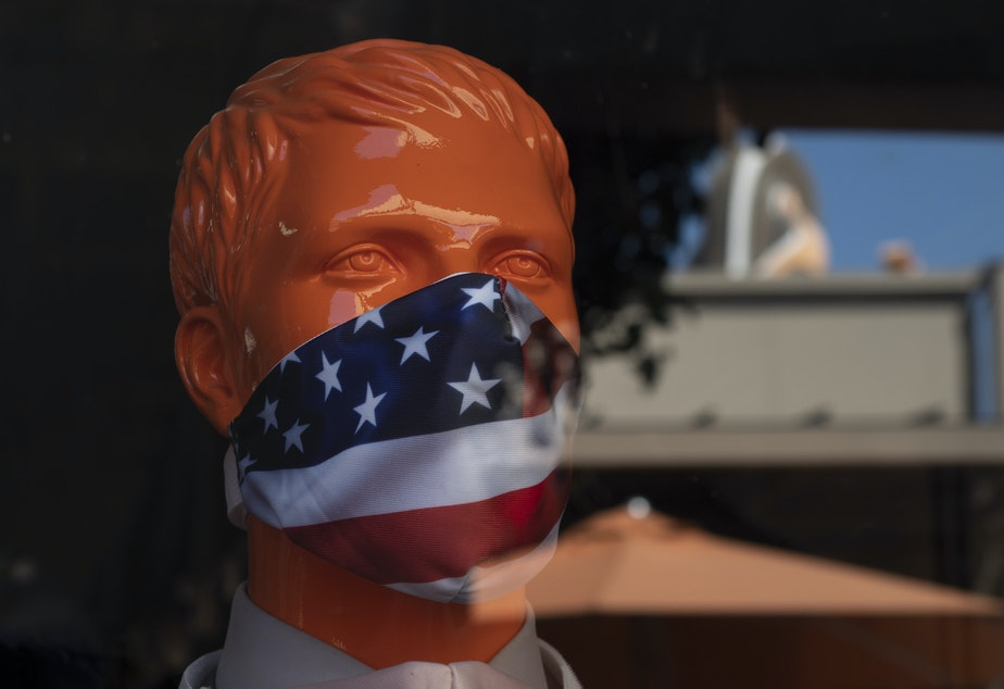 """caption: A mannequin wears a face mask at the Citadel Outlets in Commerce, Calif. Gov. Gavin Newsom on Thursday urged Californians to turn to their """"better angels"""" and use common sense over the holiday weekend by wearing a mask and skipping traditional gatherings with family and friends."""