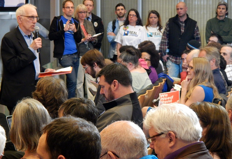 caption: Seattle City Council member Nick Licata speaks to an overflow crowd about rent control in the city council chambers.
