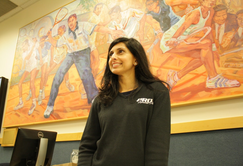 caption: Shabana Khan stands in front of a painting at Pro Sports, Bellevue, that depicts members of her family playing squash. (Shabana is the one in blue, while her brother Azam is in the center of the painting at her left).