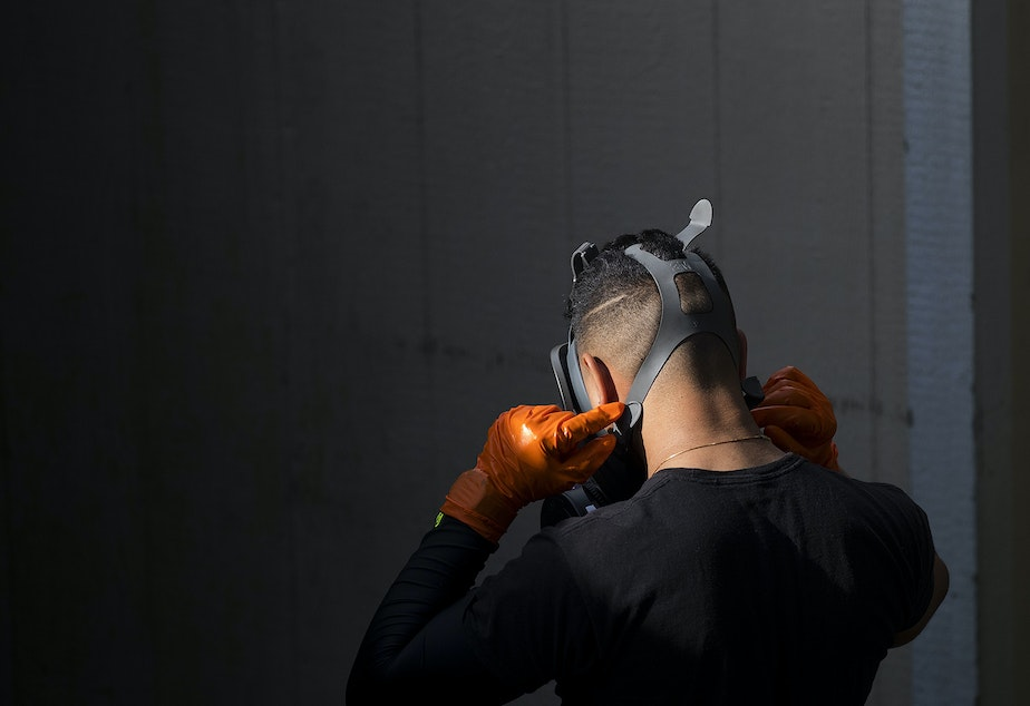 caption: A member of a Servpro cleaning crew removes a protective face mask after exiting the Life Care Center of Kirkland, the long-term care facility at the epicenter of the coronavirus outbreak in Washington state, on Wednesday, March 11, 2020, in Kirkland.