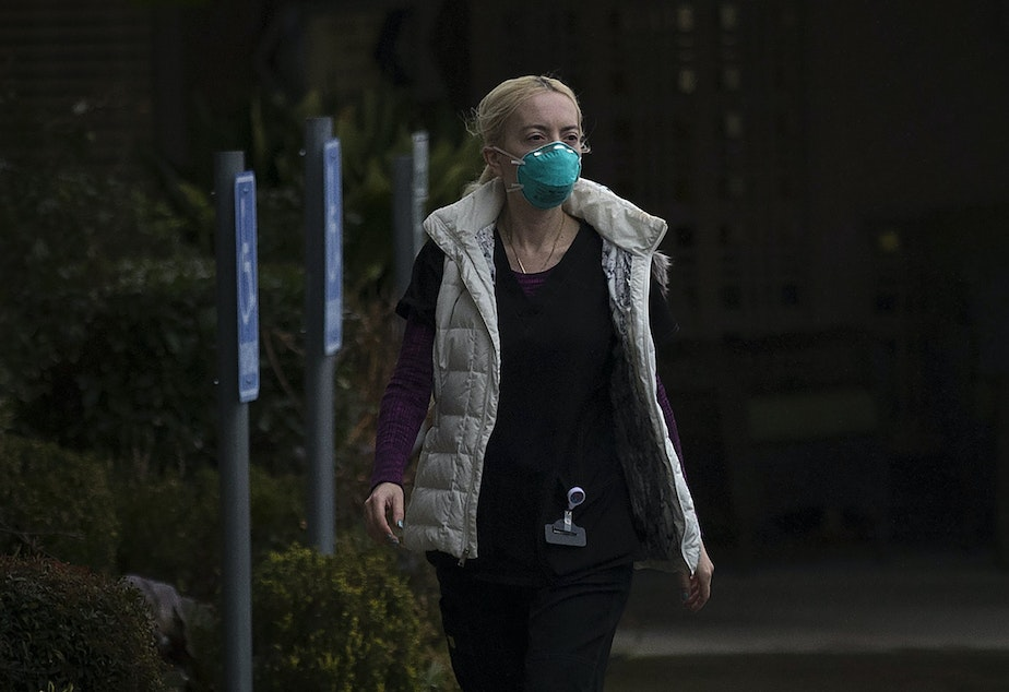 caption: An employee at the Life Care Center of Kirkland leaves the facility wearing a mask on Monday, March 2, 2020, in Kirkland. The long-term care facility is the epicenter of the coronavirus outbreak in Washington state.