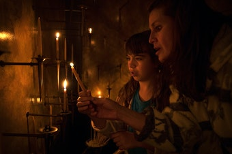 Mariela Mahoney-Armas, 9, left, and Anni Armas light candles on Thursday, June 21, 2018, during a prayer and procession for families at the border at St. James Cathedral in Seattle. Tap or click on the first image to see more.