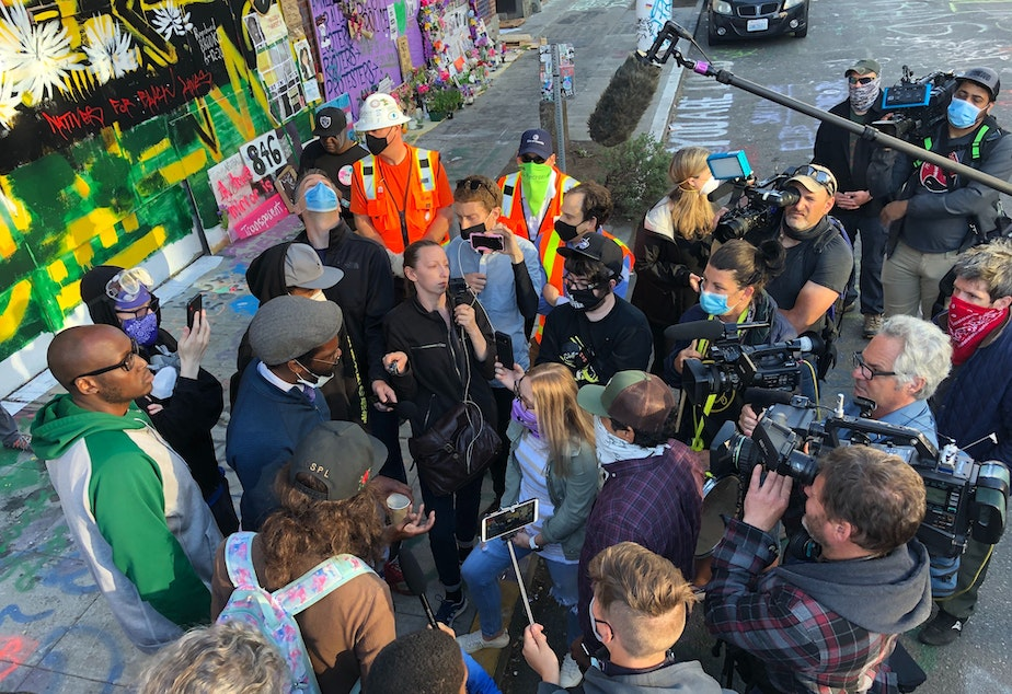 caption: Stephanie Formas from the mayor's office (center in light blue shirt and purple mask) speaks with protesters Friday morning in the CHOP while city workers were trying to remove road barriers.