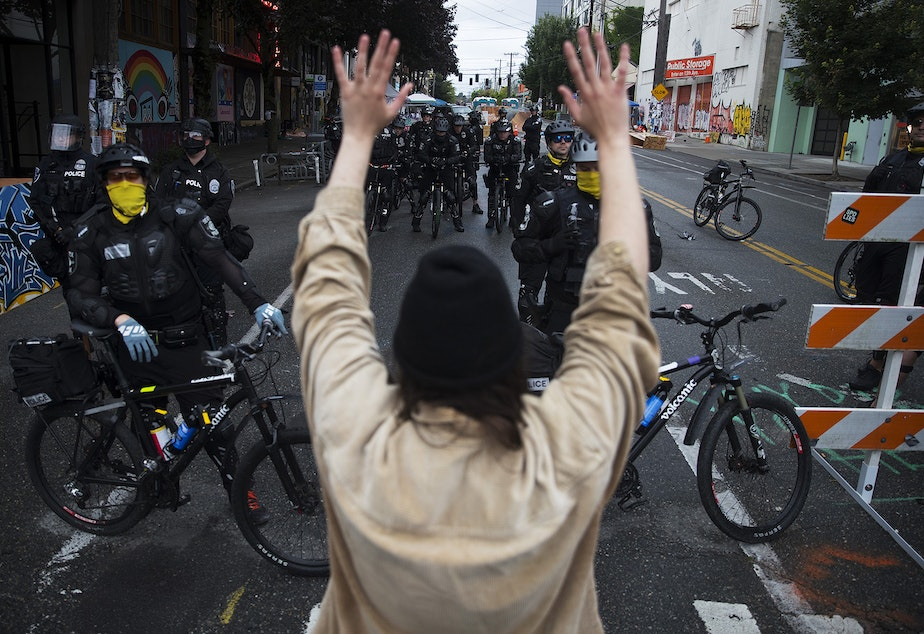 caption: A protesters raises their hands in the air while standing at a police line outside of the East Precinct building after the Capitol Hill Organized Protest zone was cleared by Seattle Police Department officers early Wednesday morning, July 1, 2020, at the intersection of 12th Avenue and in East Pike Street in Seattle.