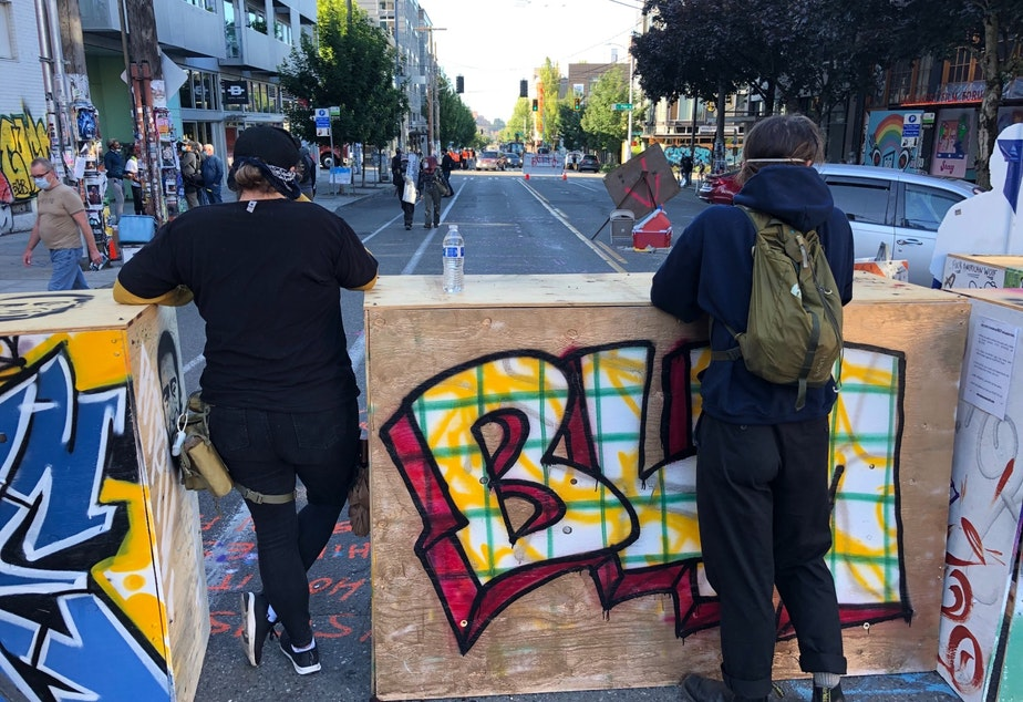 caption: Protesters watch over the CHOP's eastern barrier on 2th Avenue