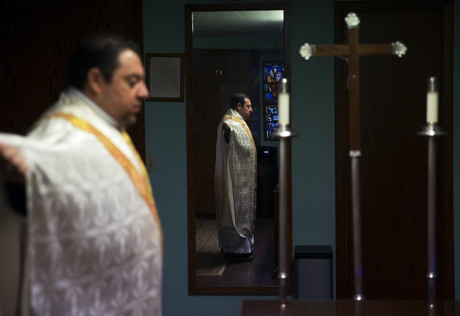 caption: Father Jose Alvarez gets ready for a live-streamed daily mass in Spanish on Friday, April 24, 2020, at Holy Family Roman Catholic Church in White Center.