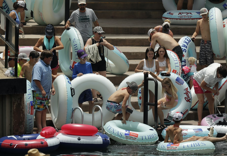 "caption: Tubers prepare to float the Comal River in New Braunfels, Texas, on Thursday. Texas Gov. Greg Abbott said Wednesday that the state is facing a ""massive outbreak"" of the coronavirus and that some new local restrictions may be needed to preserve hospital space for new patients."
